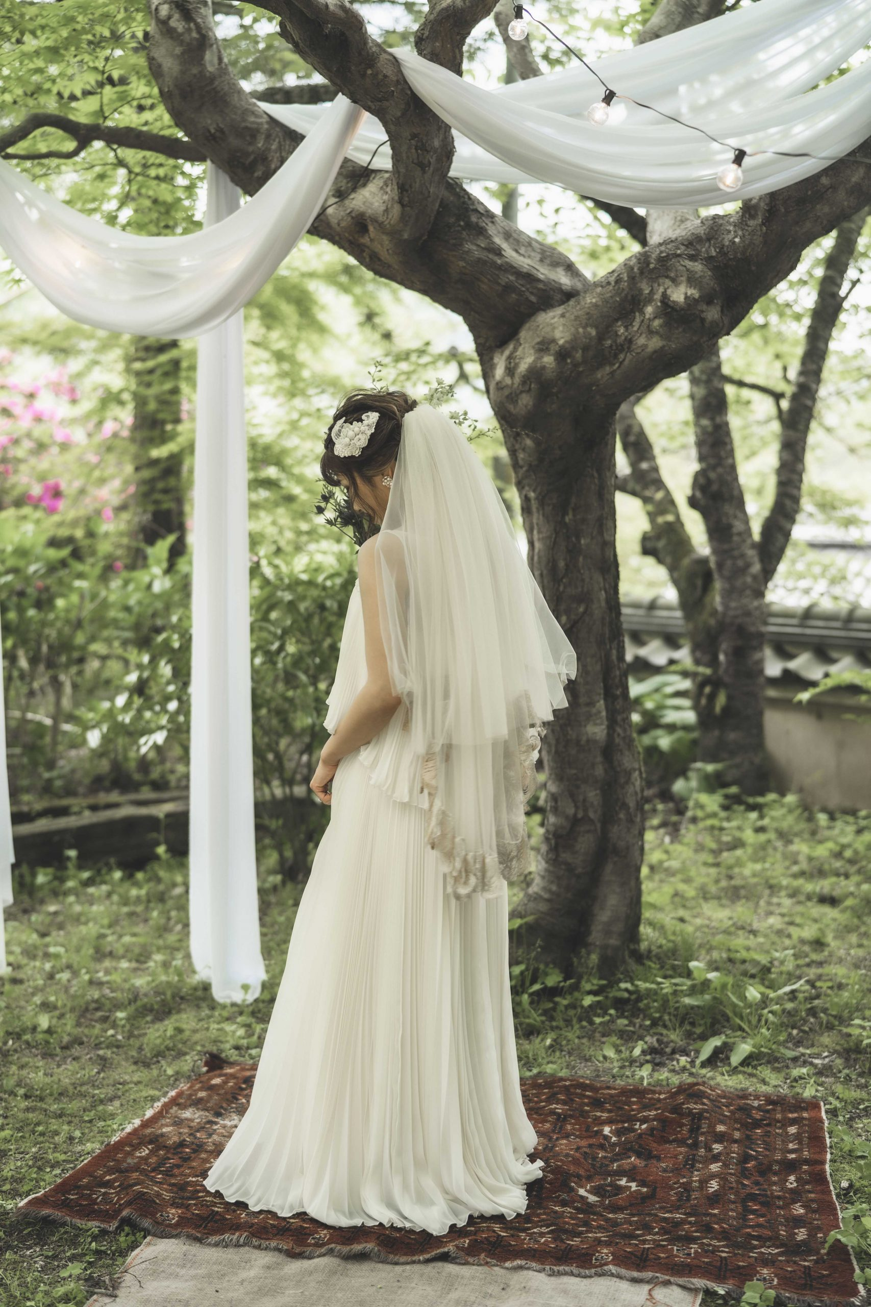 ガーデンセレモニーでの花嫁とアンティークキリム