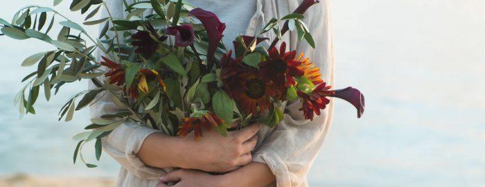フレッシュな花を抱いた女性