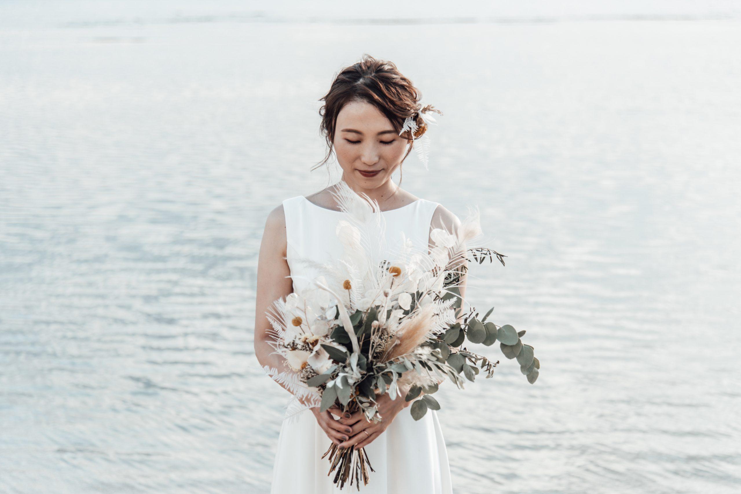 沖縄のビーチでウェディングブーケを持つ花嫁