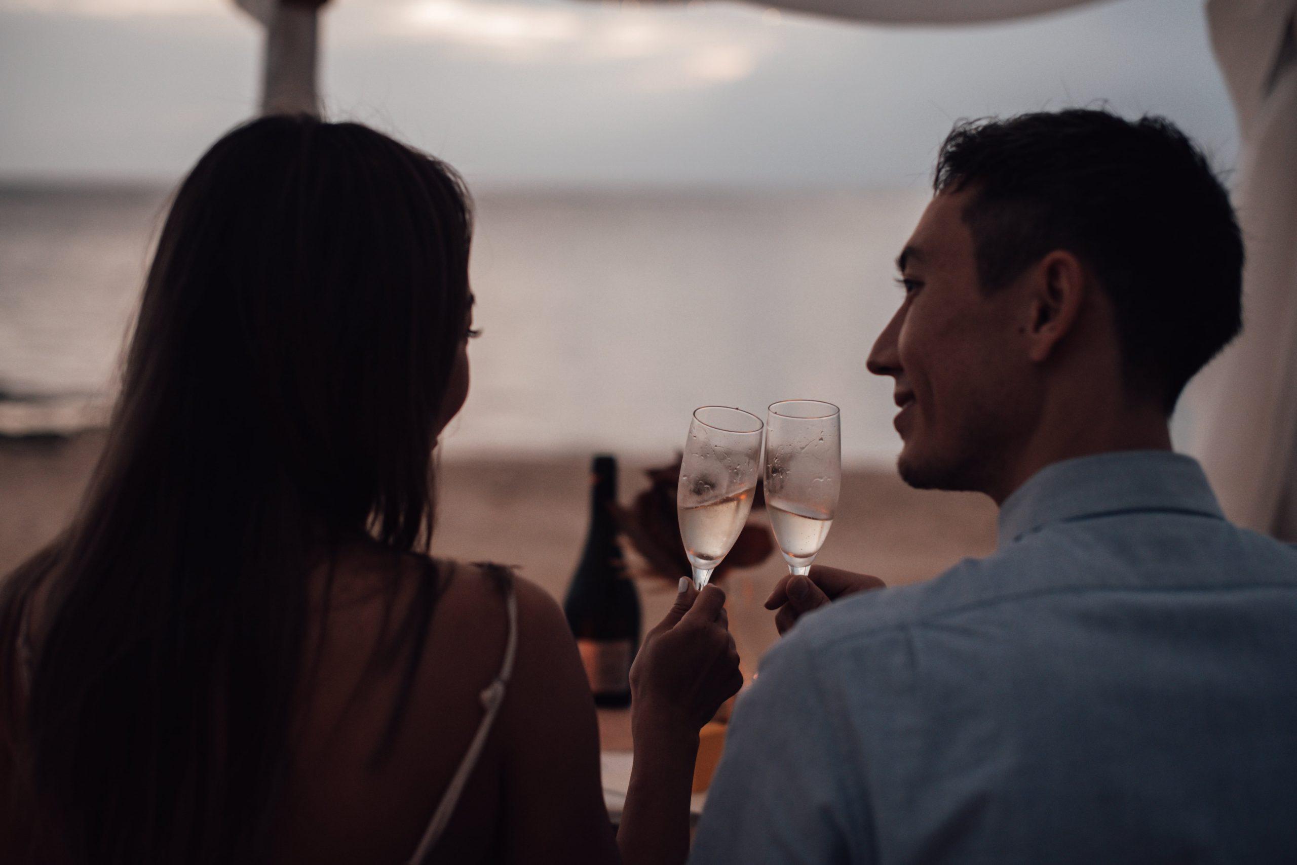 沖縄のビーチでサンセットを見ながら乾杯するカップル